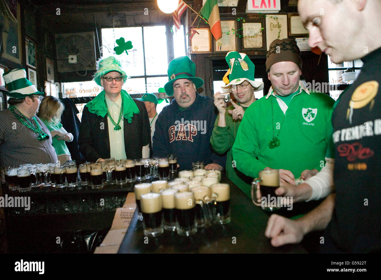 Barely awake customers celebrate St Patrick's day at McSorley's pub in New York City, 17 March 2006. - Stock Image