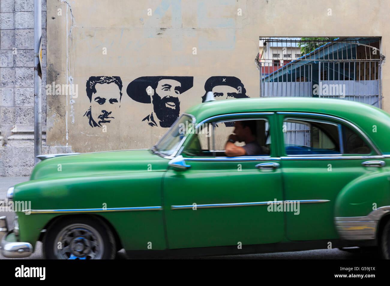 Green classic car passes a wall mural of (l) Julio Antonio Mella, Camilo Cienfuegos (m) and Che Guevara (r) in Havana, Stock Photo