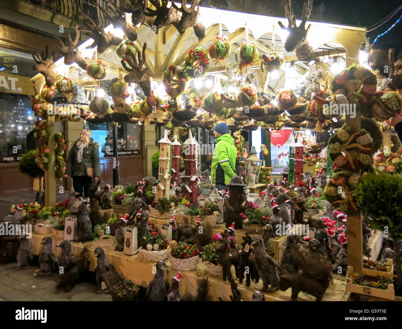 Night scene with people shopping at market stall on Christmas market in Manchester, England, United Kingdom - Stock Image