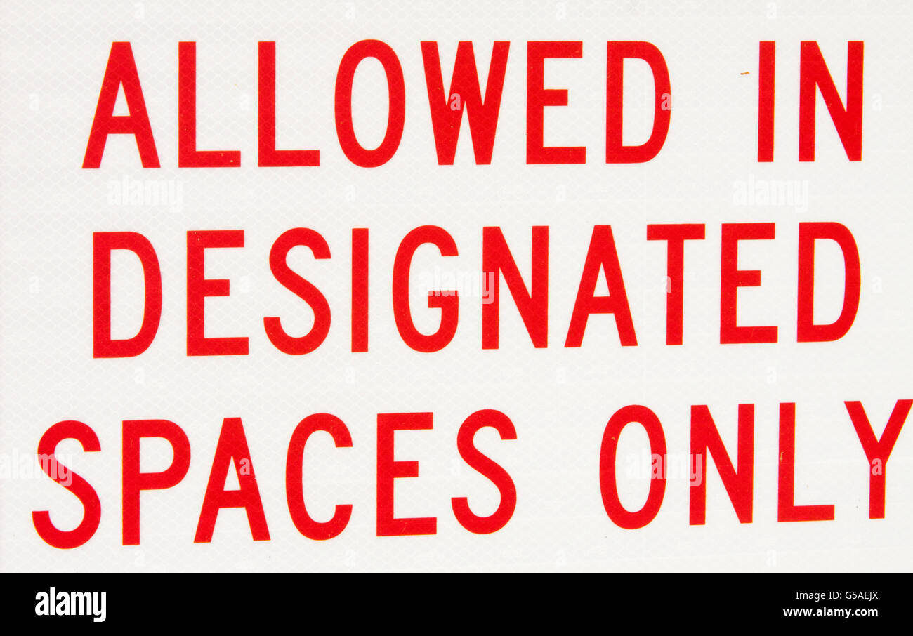 Allowed in Designated Spaces Only Sign - Stock Image