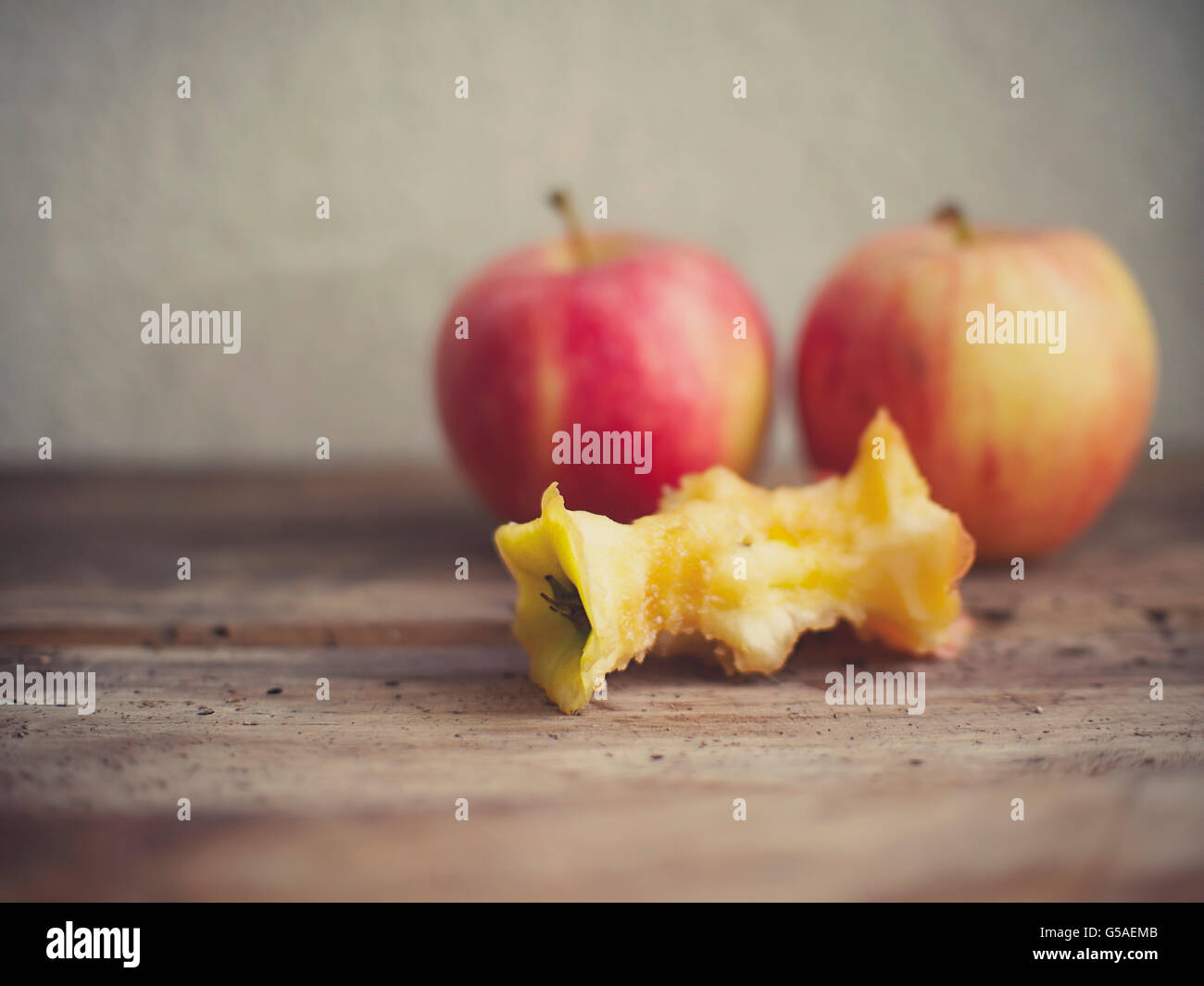 An apple core with two whole apples on the background. Vintage film style applied. - Stock Image