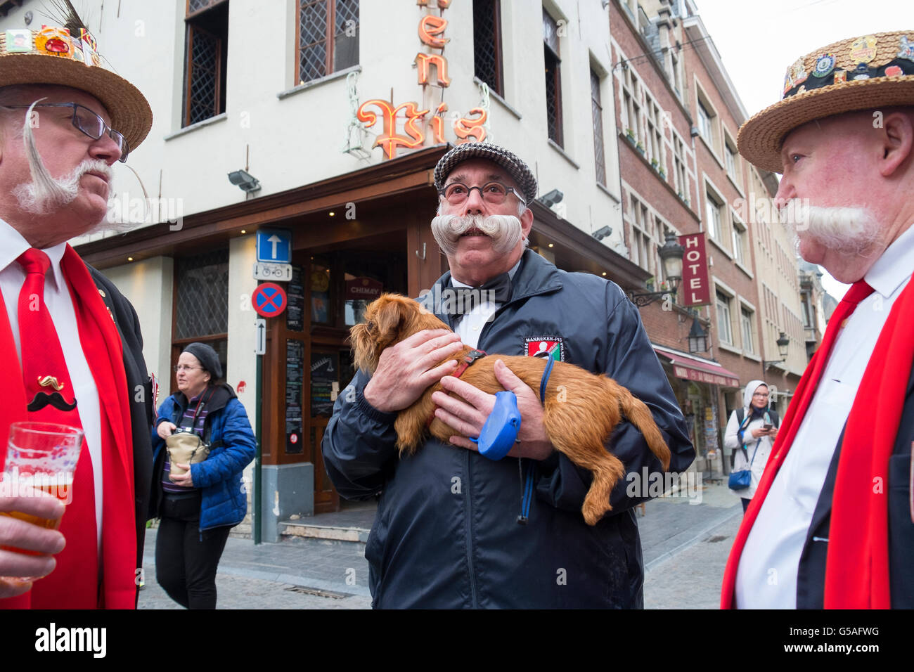 man moustache carries carry carrying dog arms hand - Stock Image
