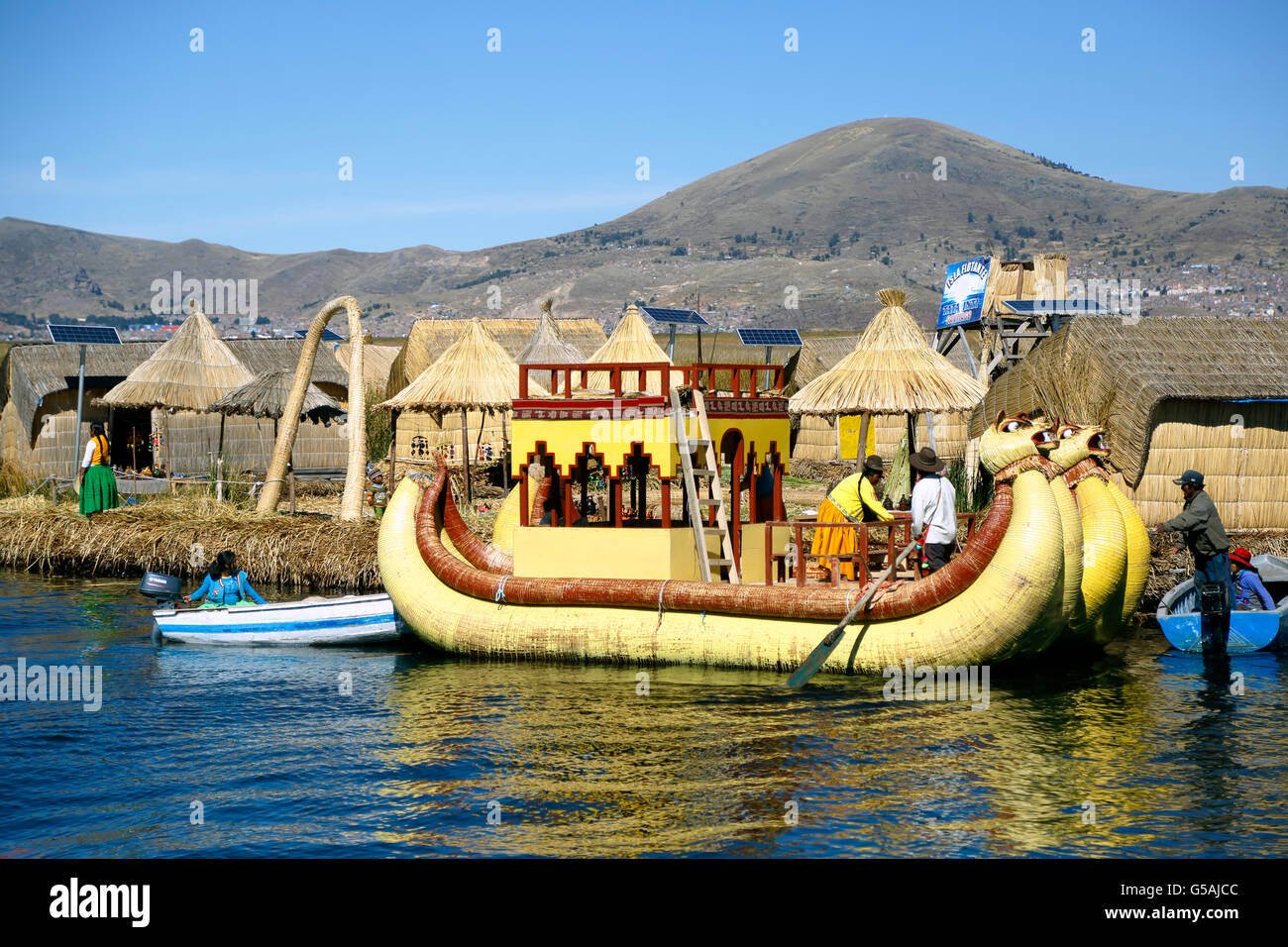 Yellow totora reed boat and houses on totora reed island, Uros Islands, Lake Titicaca, Puno, Peru - Stock Image