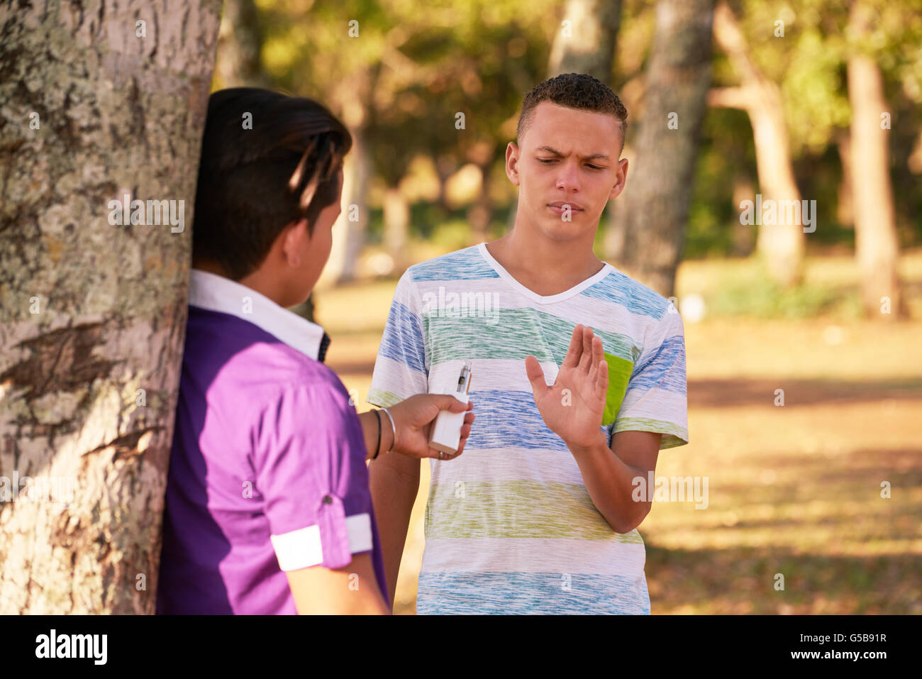 Kids in park smoking electronic cigarette. Concept of smoking and social issues with young teenagers - Stock Image