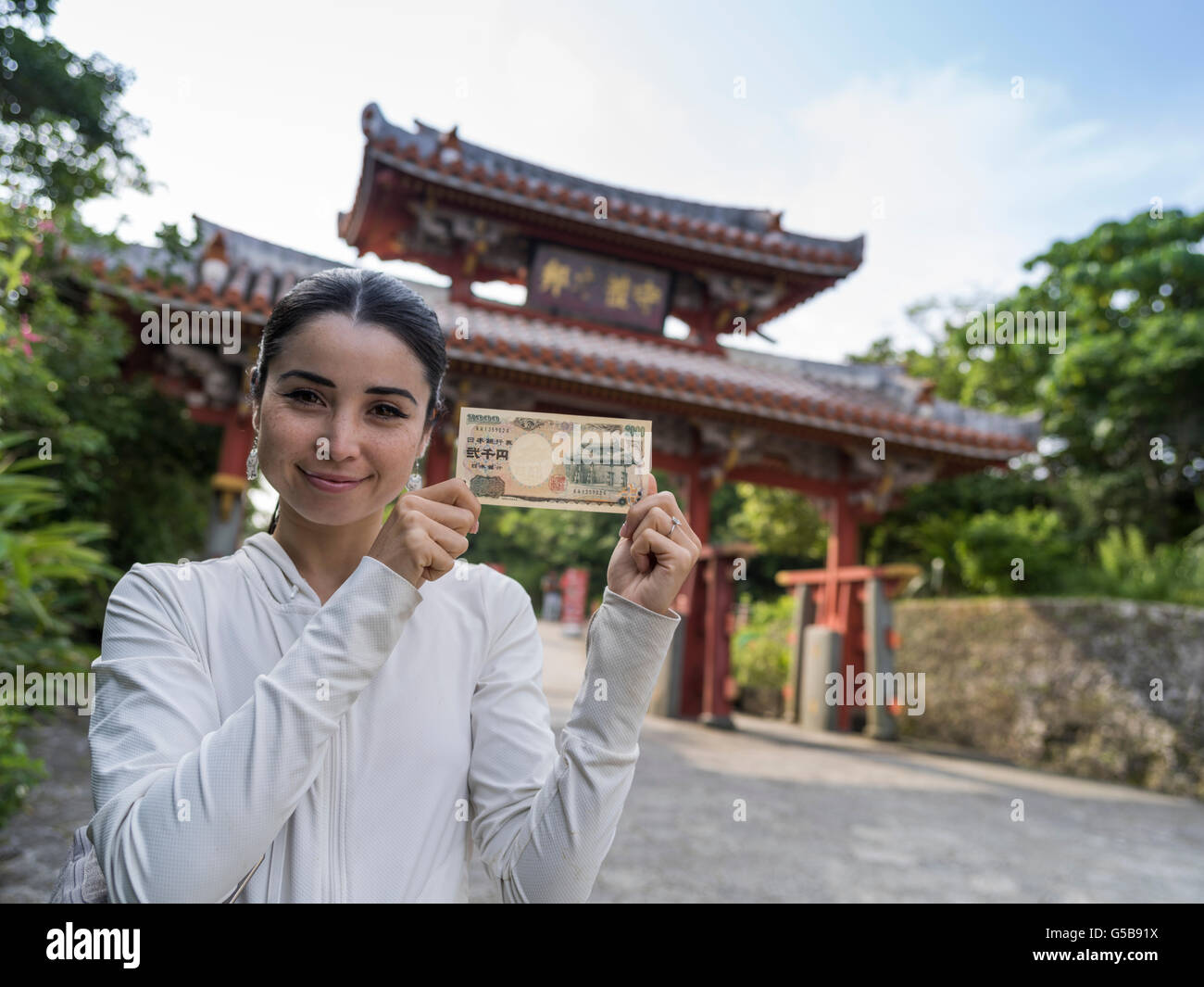 Visitor (model released) with Japanese 2000 yen note in front of the Shureimon Gate at Shuri Castle, Naha City, - Stock Image