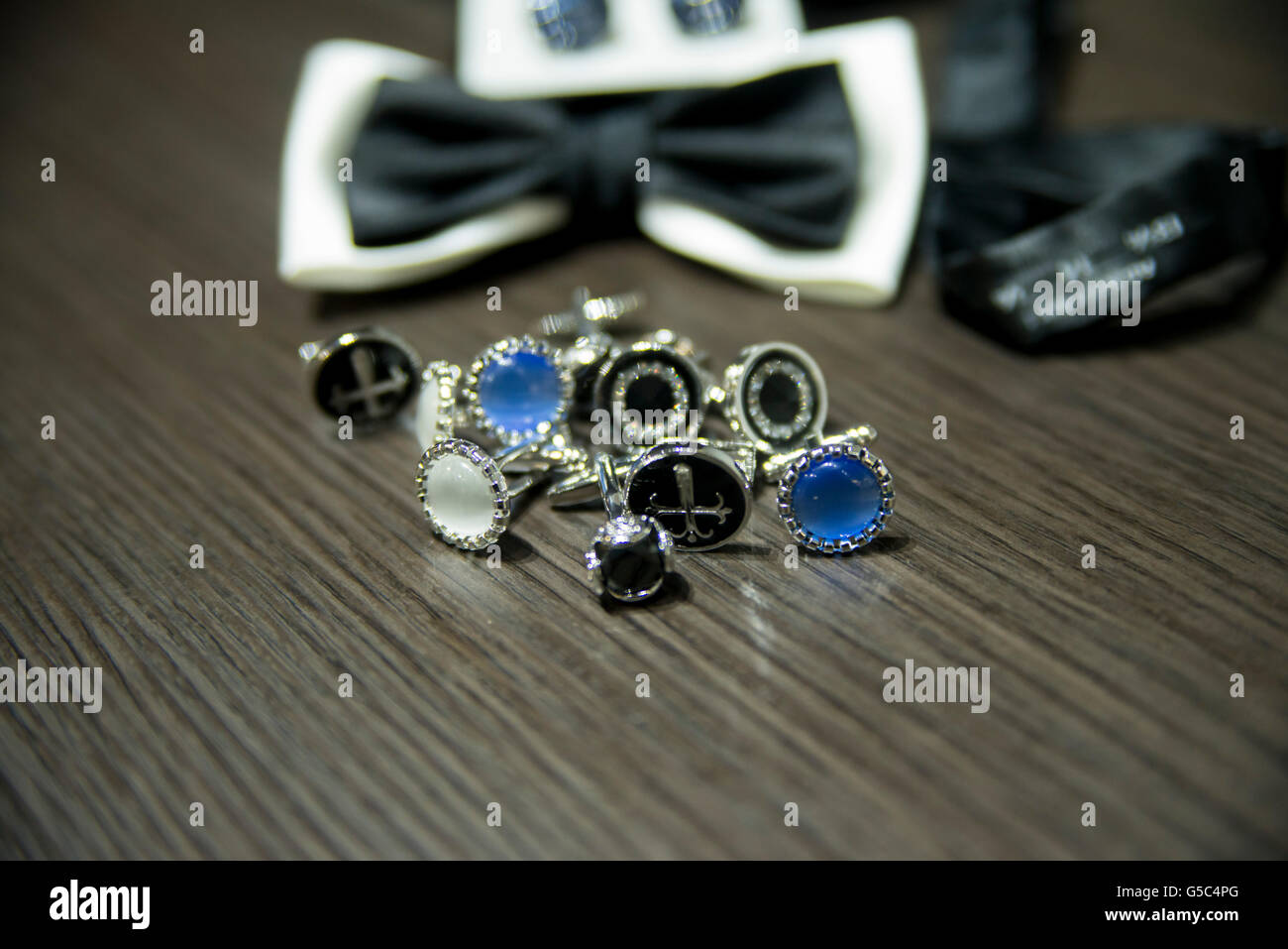 Assorted cuff links on wooden table with bow tie and accessories in the background - Stock Image