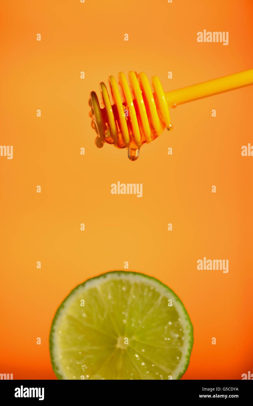 Honey flowing on lemon over yellow background Stock Photo