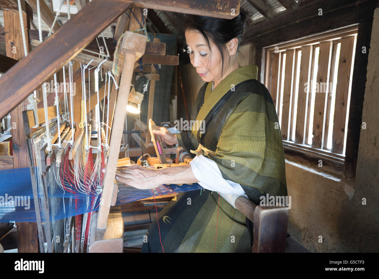 Traditional weaving on a loom at Ryukyu Mura, Okinawa, Japan - Stock Image