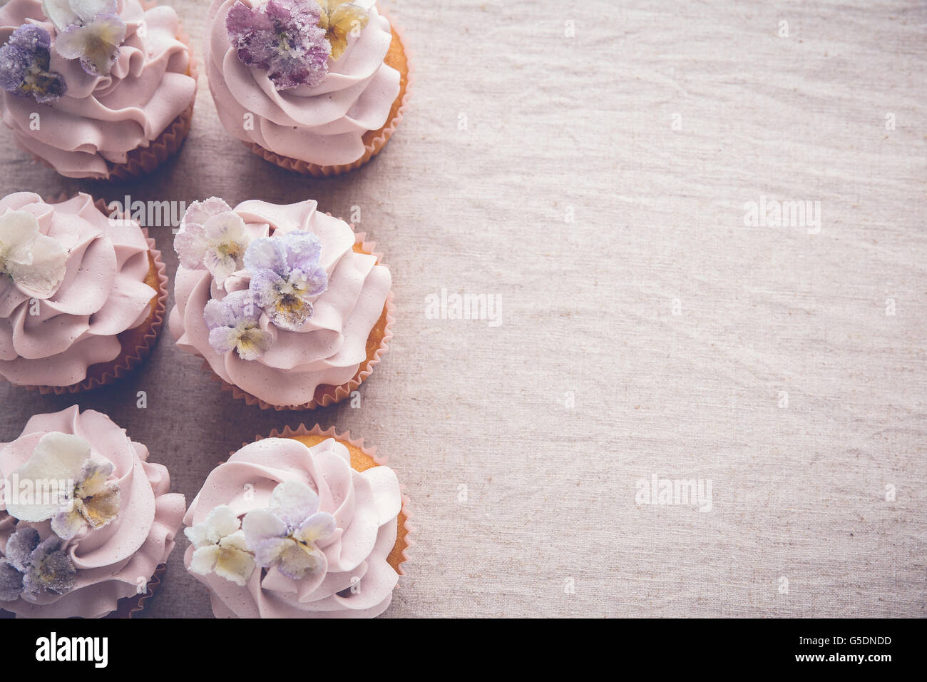 Purple cupcakes with sugared edible flowers copy space background, vintage toning - Stock Image