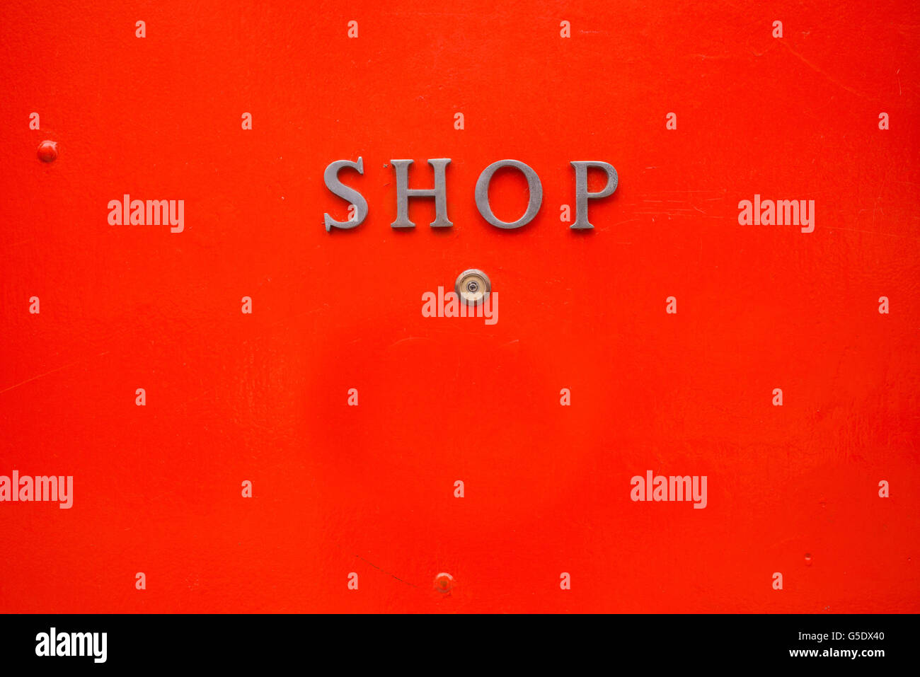 Shop written in metal letters on a bright red door background - Stock Image