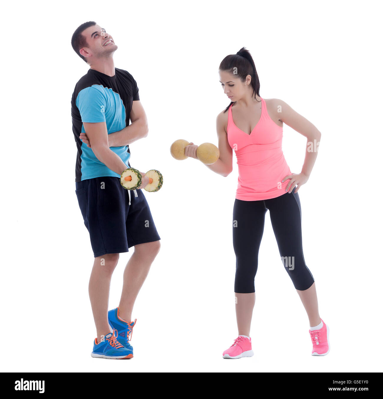 Fit couple working out with dumbbells created with fuits and vegetables - Stock Image