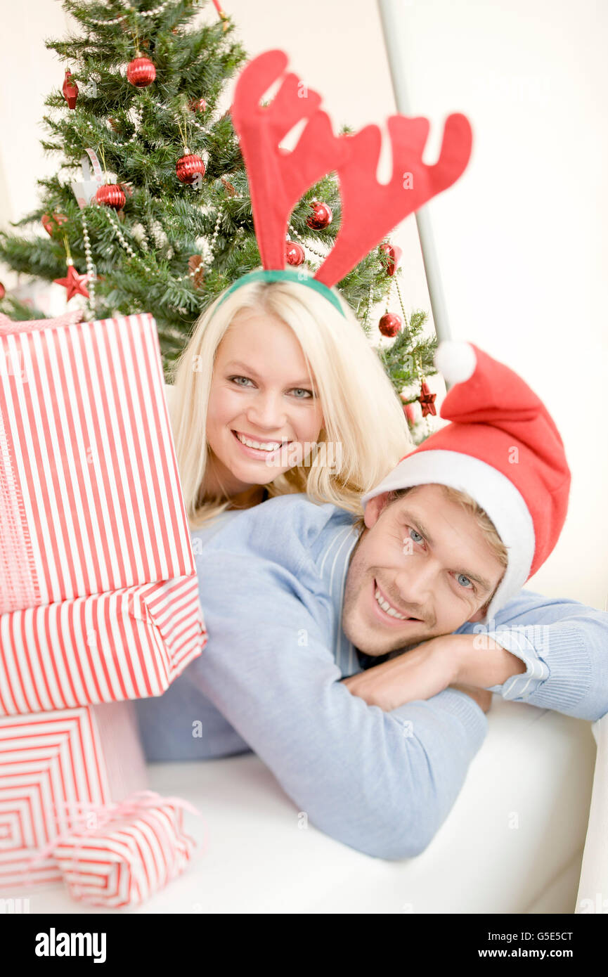 Young woman with moose antlers and young man with Santa hat next to Christmas presents in front of a Christmas tree - Stock Image