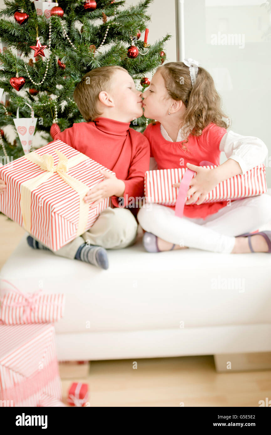 Brother and sister with Christmas present kissing Stock Photo