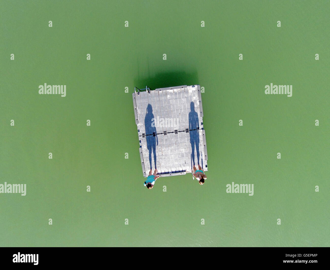 Two swimmers (and shadows) standing on pontoon, Bannockburn Inlet, Lake Dunstan, Central Otago, New Zealand - drone - Stock Image