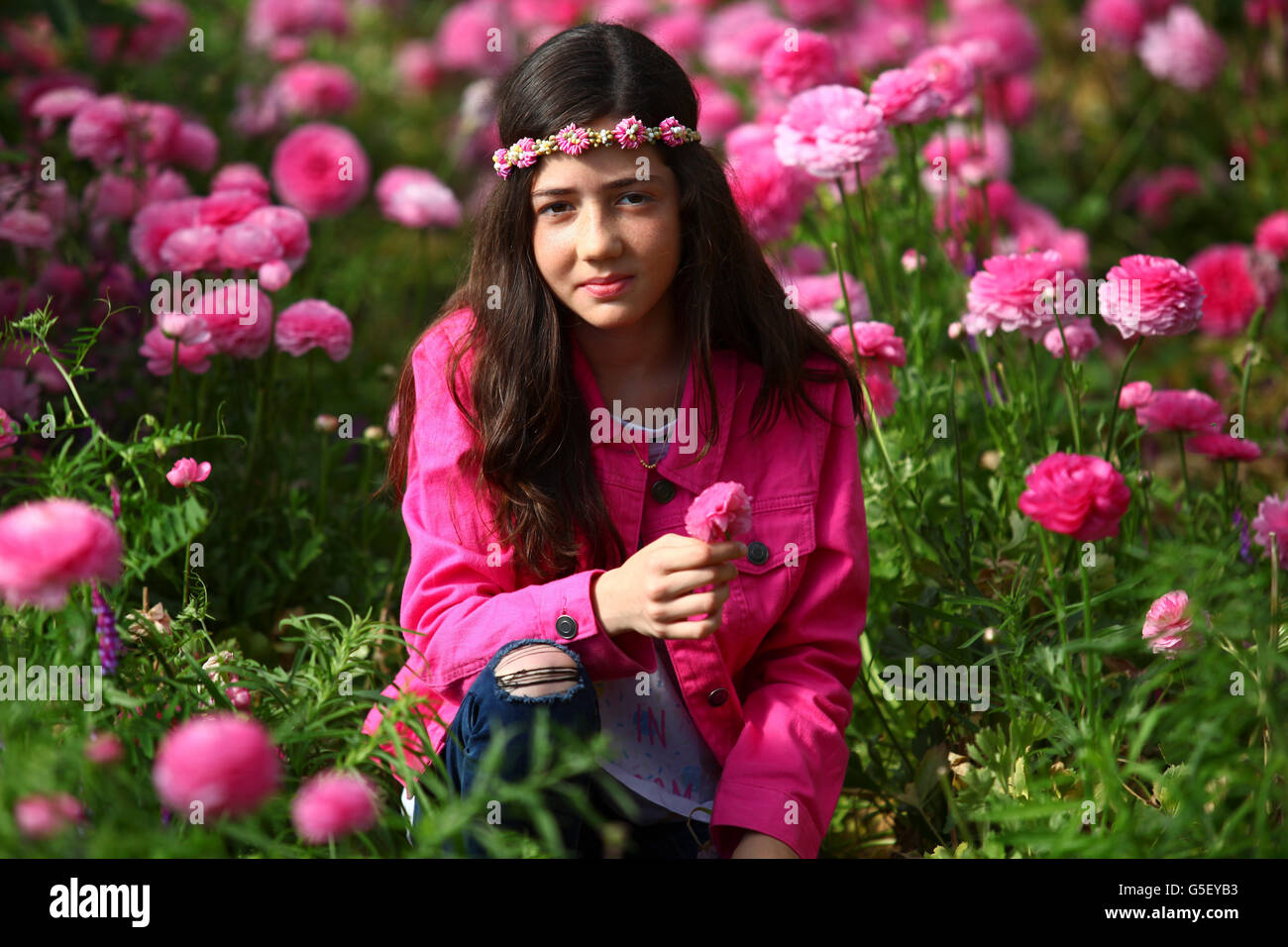 Young preteen girl of 12 in a hothouse of pink flowers Stock Photo