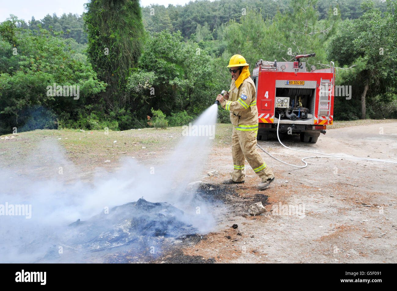 Fireman in protective clothing extinguishes a fire as part of a fire fighting drill - Stock Image