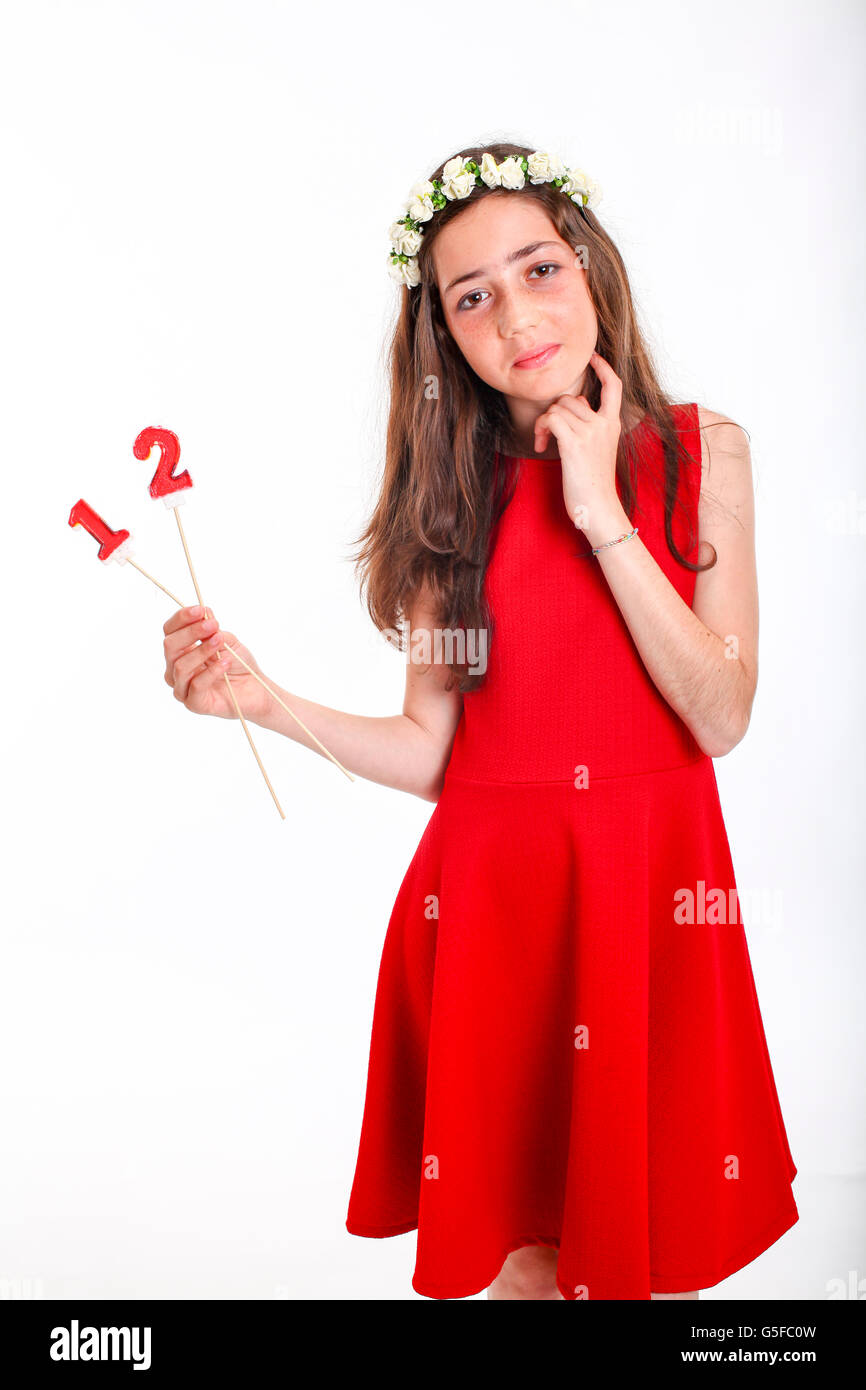 Pre-teen girl in red dress and wreath celebrates twelve - Stock Image