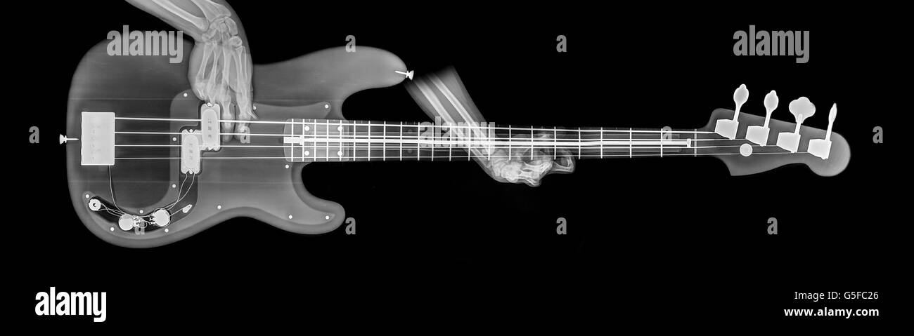 hands play base guitar under x-ray - Stock Image