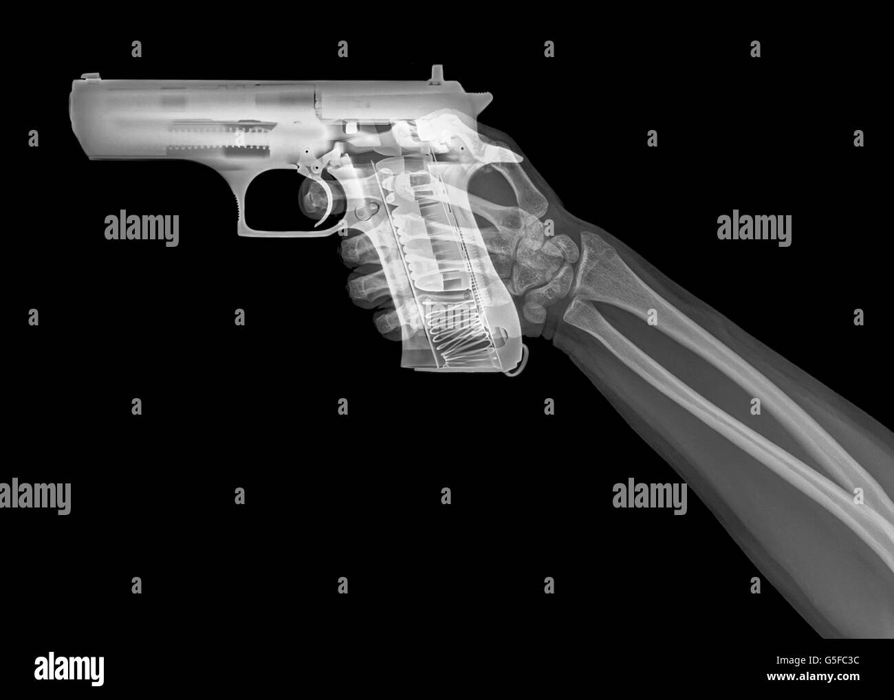 hand holds a gun under x-ray - Stock Image