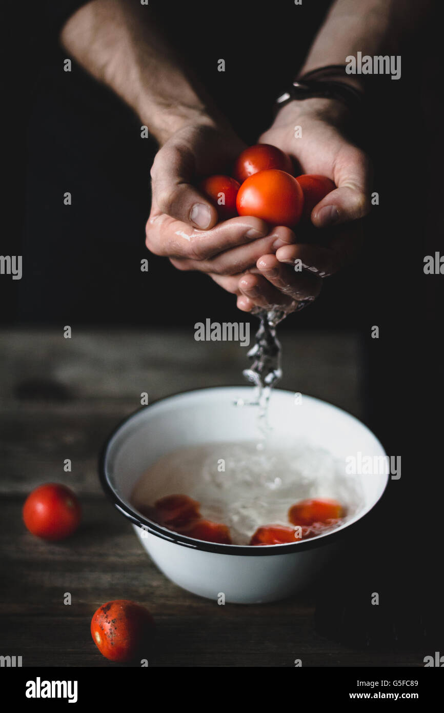 Male chef washing tomatoes. Tomatoes in hands. - Stock Image