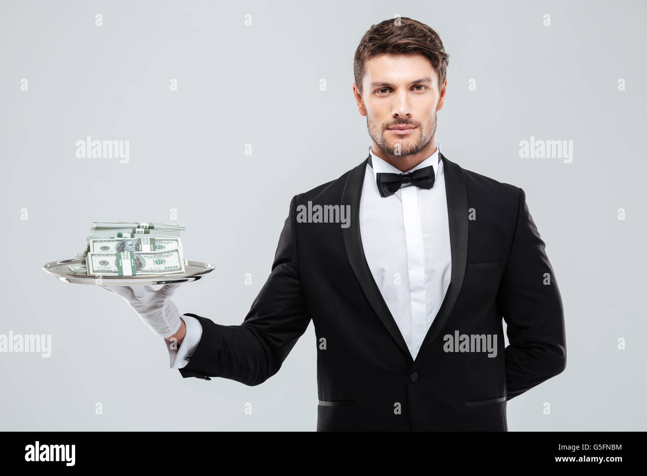 Handsome young waiter in tuxedo standing and holding money on tray Stock Photo