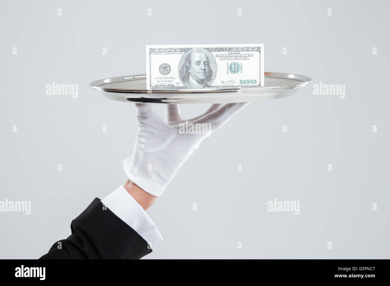 Hand of waiter in white glove holding tray with dollars - Stock Image
