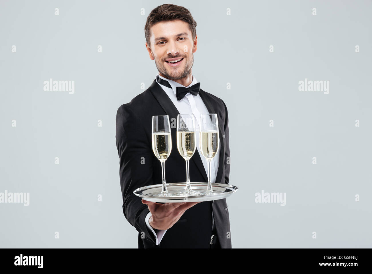 Cheerful young butler in tuxedo smiling and offering champagne - Stock Image