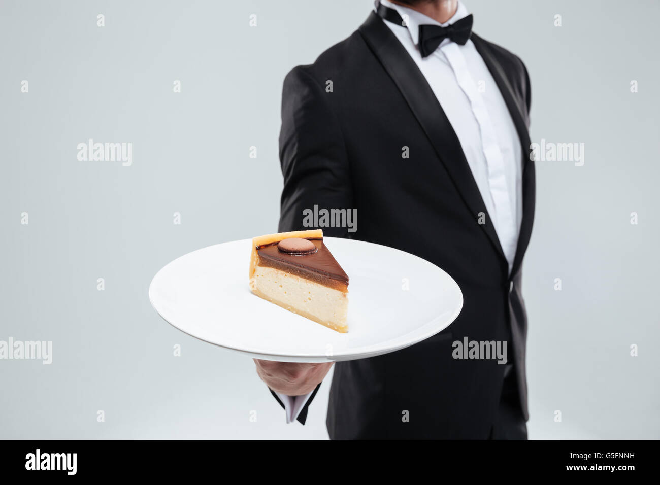 Waiter in tuxedo with bowtie holding plate with piece of