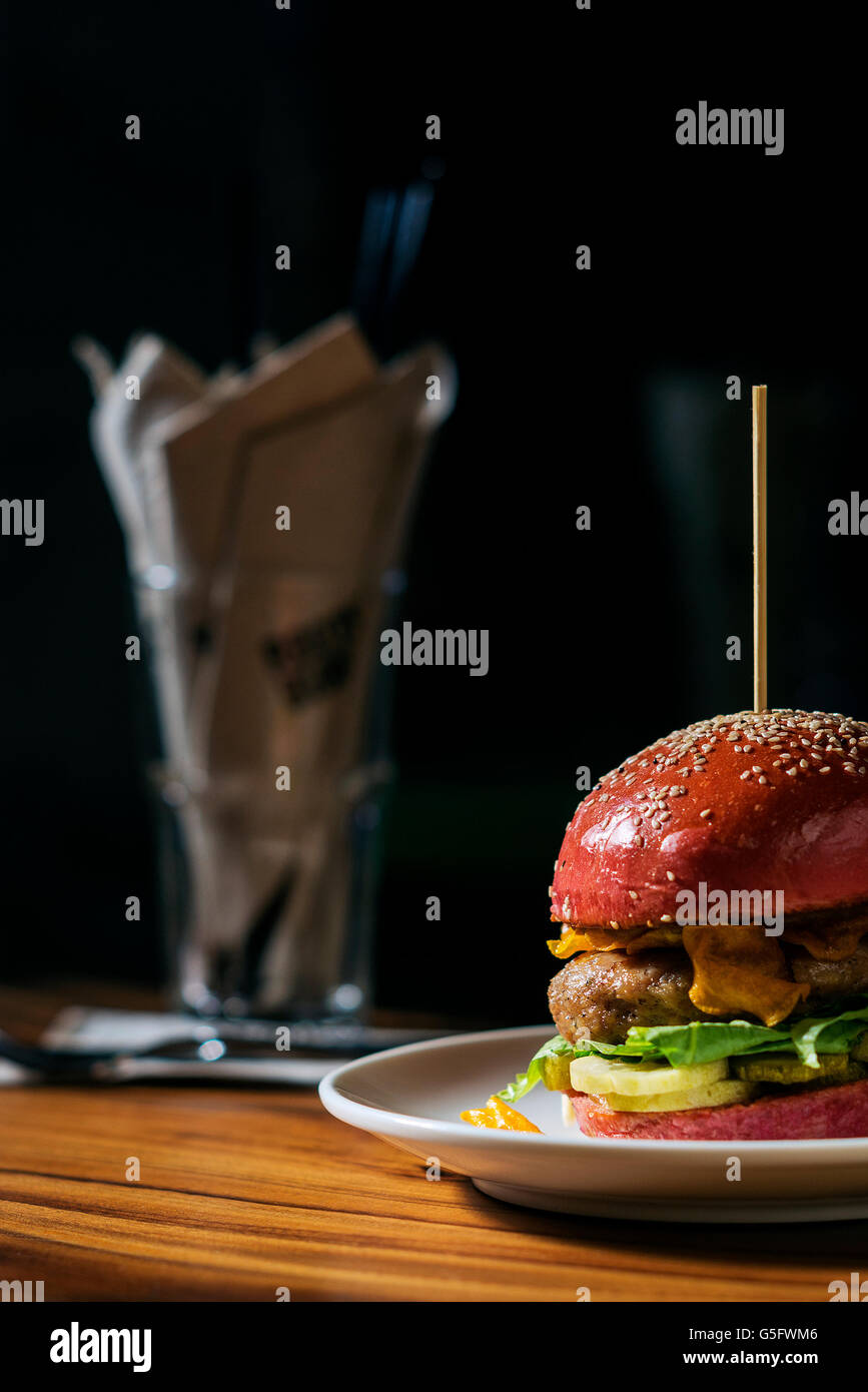modern gourmet trendy chicken burger in beetroot bun - Stock Image