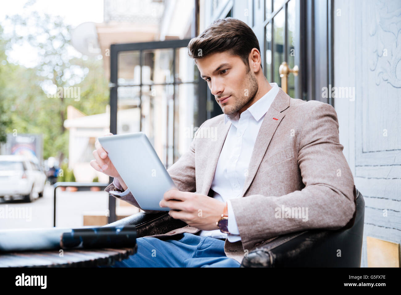 Young handsome man with tablet pc touch in a cafe outdoor - Stock Image
