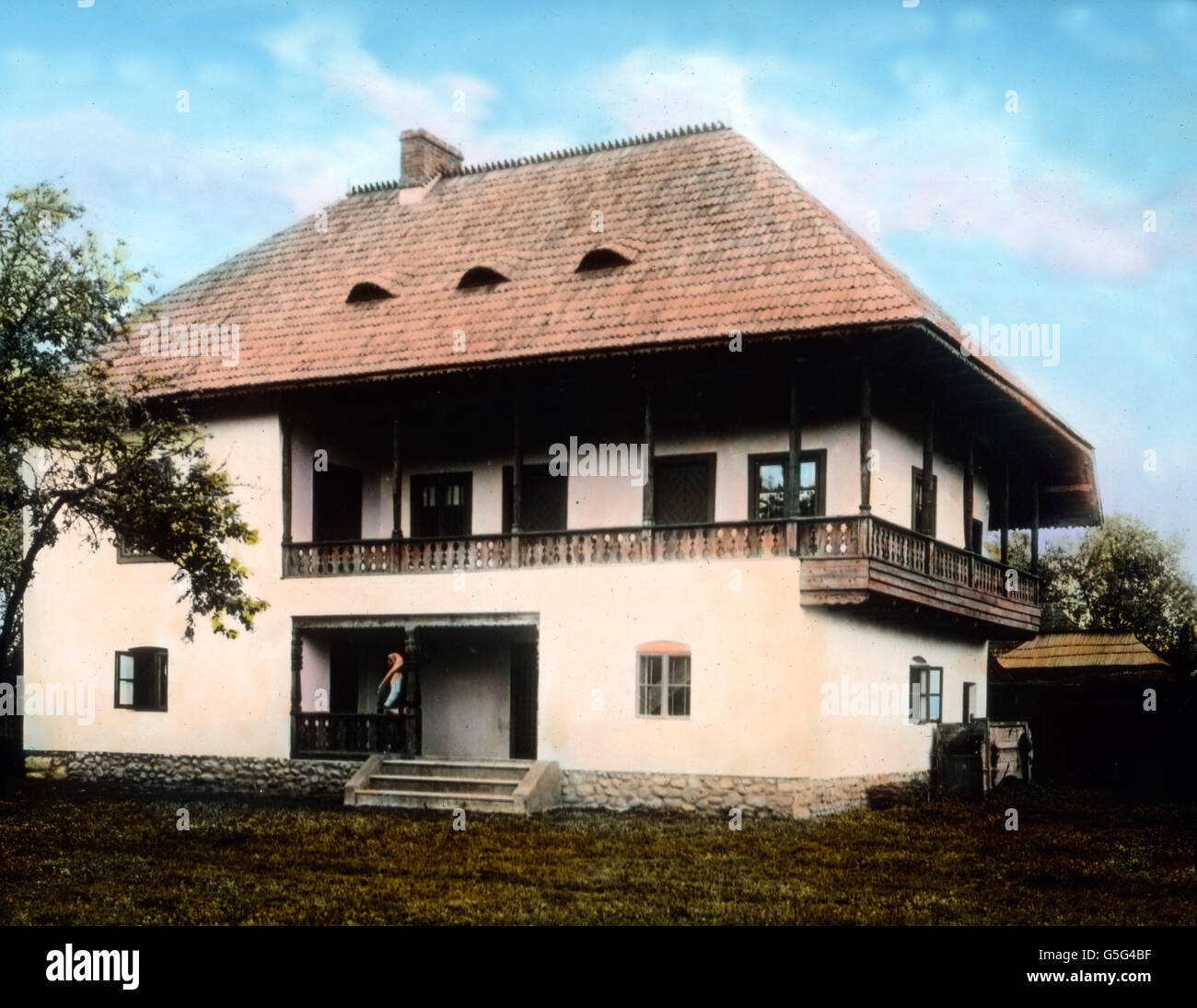 Haus eines wohlhabenden Bauern. The house of a wealthy farmer. Romania, Southeastern Europe, Balkan, history, historical, 1910s, 1920s, 20th century, archive, Carl Simon, hand coloured glass slide, house, architectire, modern, woman, standing, entrance, nice Stock Photo