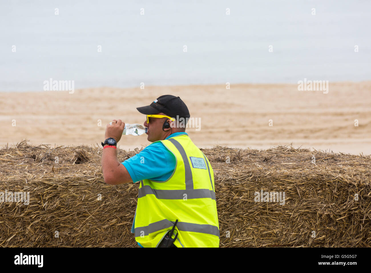 Marshall wearing hi vis vest and drinking bottle of water at Bournemouth Wheels Festival in June - Stock Image