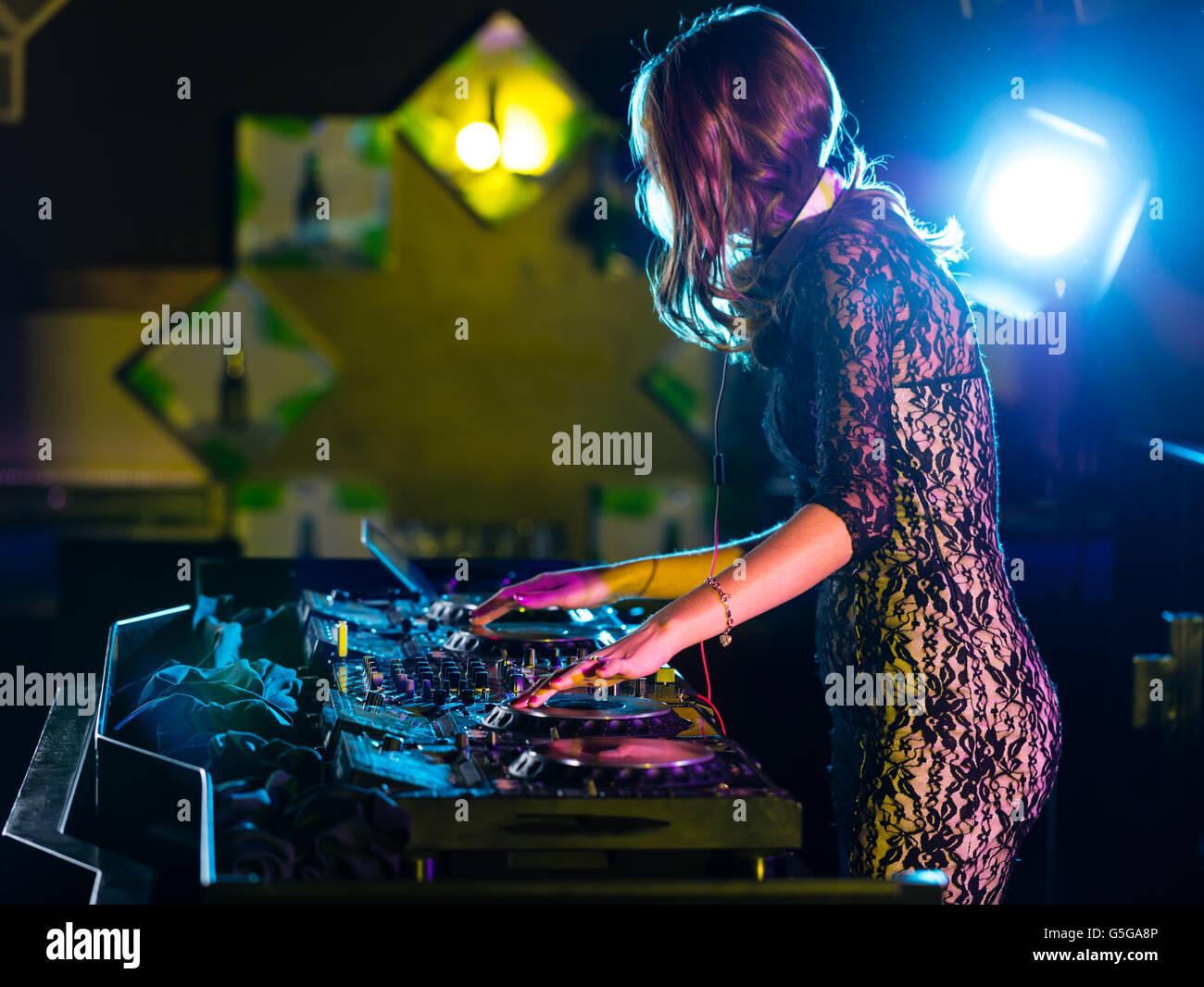 Disc jockey brunette girl mixing electronic music in club - Stock Image