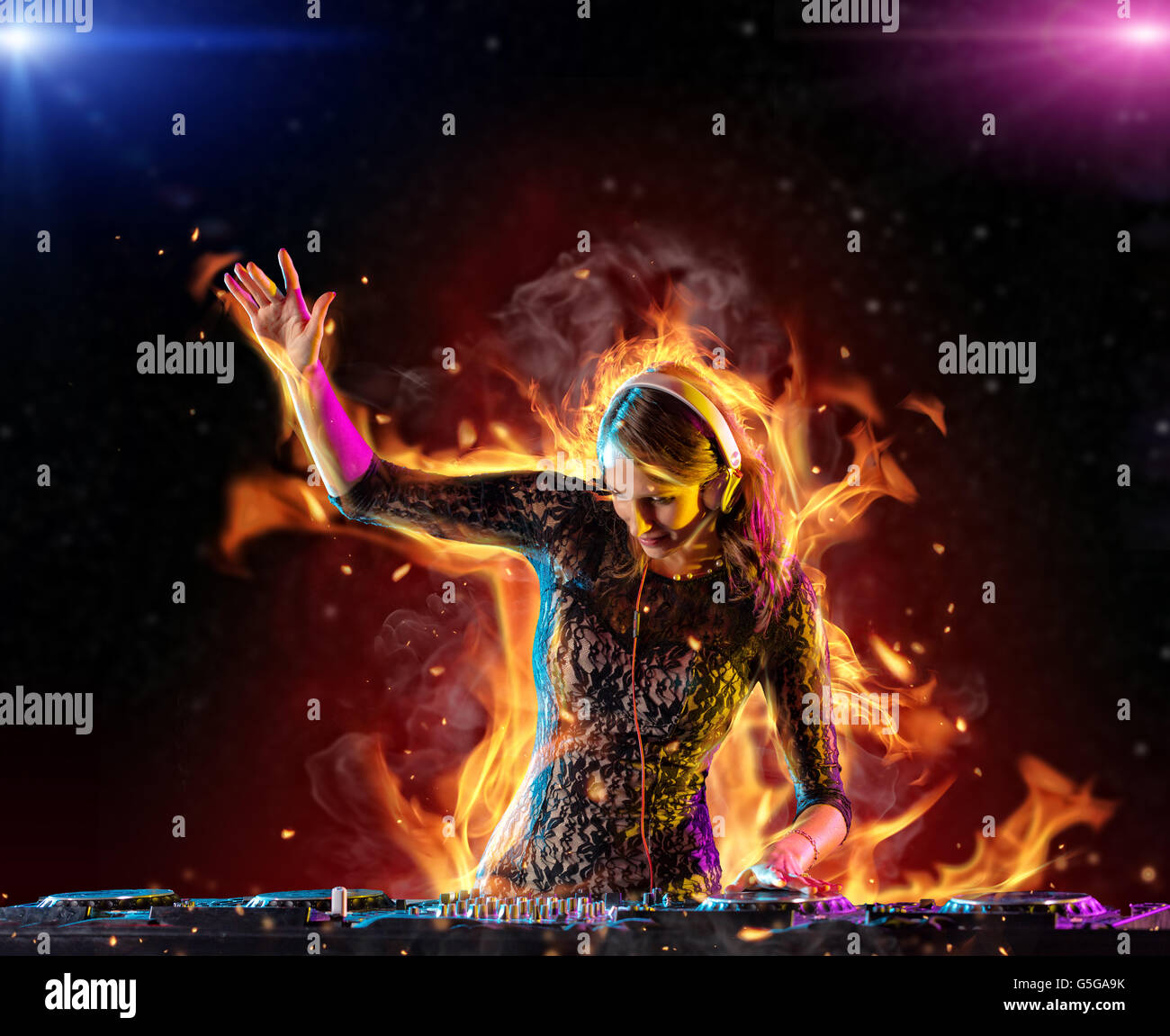 Disc jockey brunette girl mixing electronic music with fire flames around - Stock Image