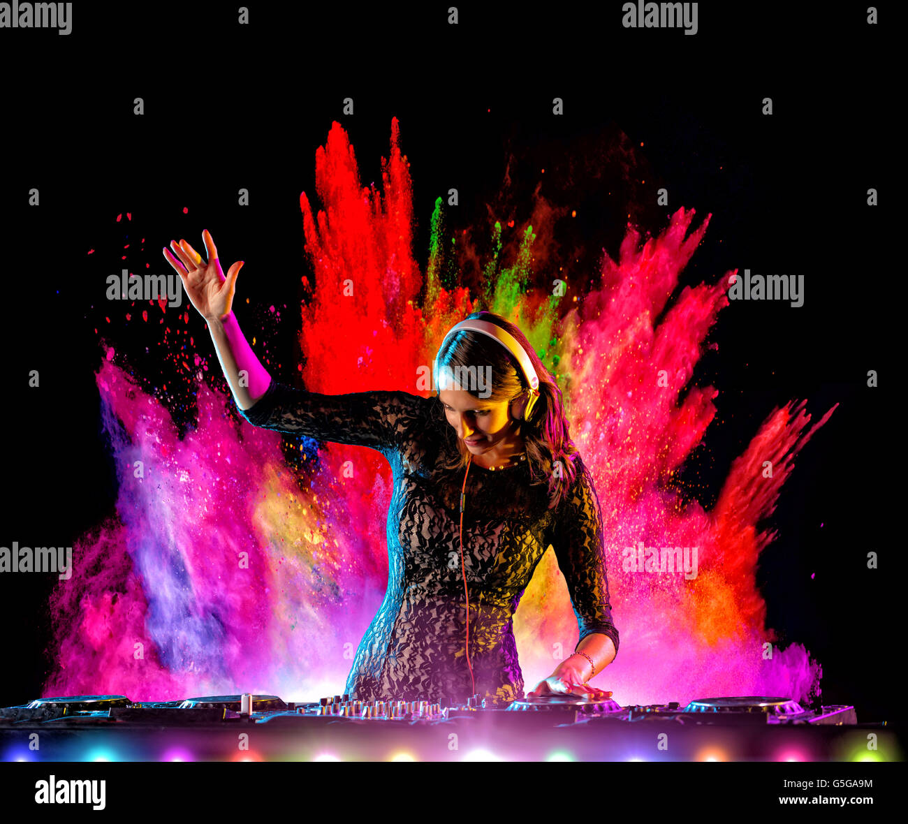 Disc jockey brunette girl mixing electronic music with colored powder explosion on background - Stock Image