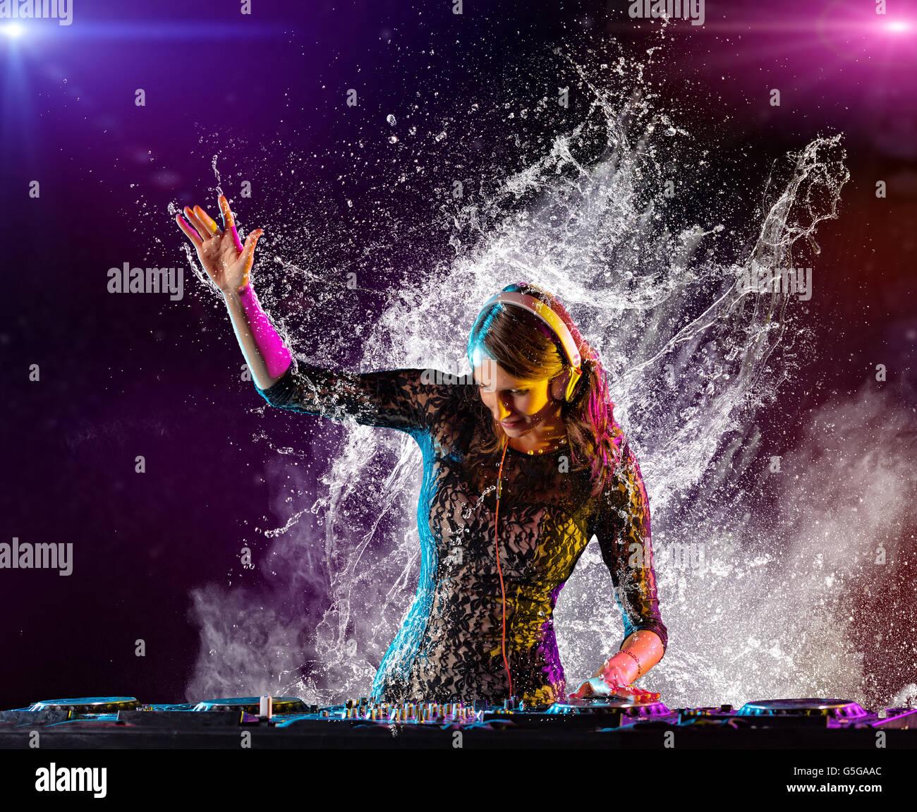 Disc jockey brunette girl mixing electronic music and splashing water around - Stock Image