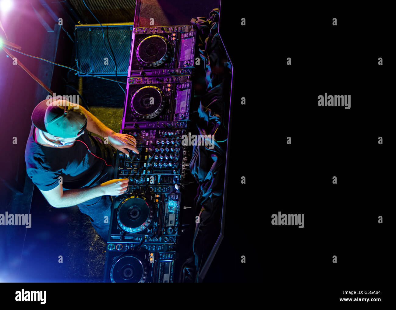 Disc jockey mixing electronic music in club. Shot from aerial percspective. Copyspace for text - Stock Image