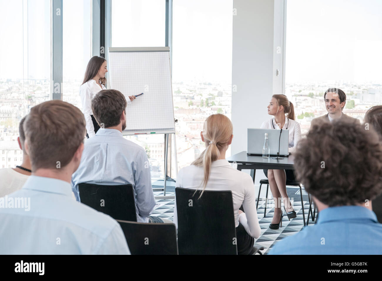 Business woman speaking at presentation and pointing to white board - Stock Image