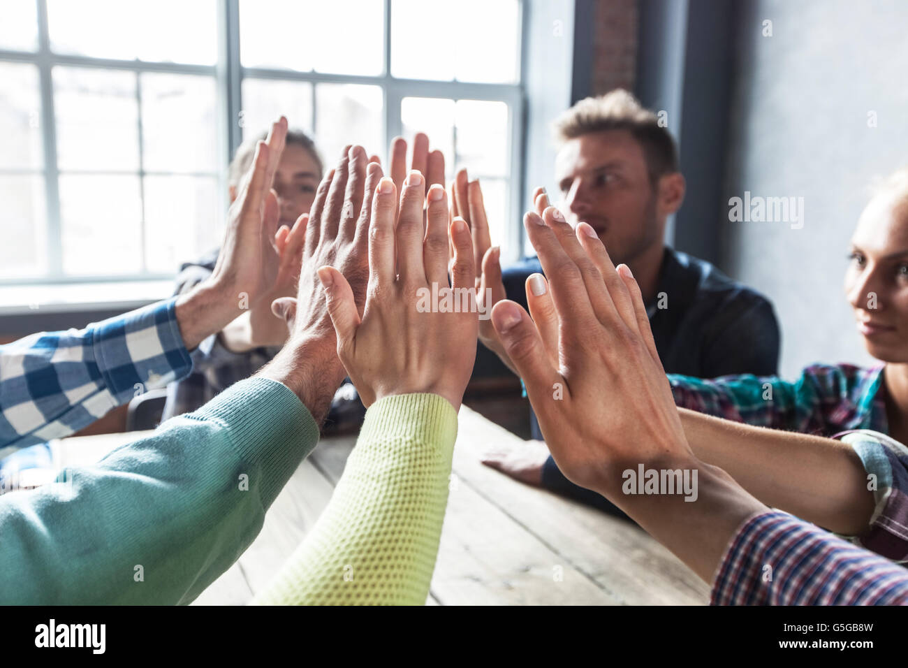 Modern business meeting concept, people on casual clothes sitting around wooden table and give high five - Stock Image