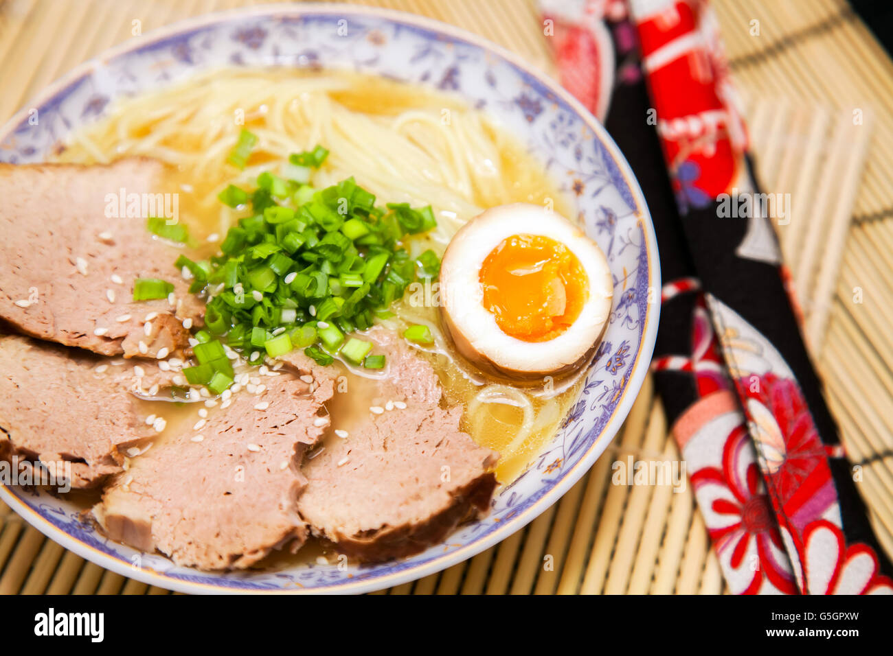 Salt ramen garnished with meat, egg and spring onion - Stock Image