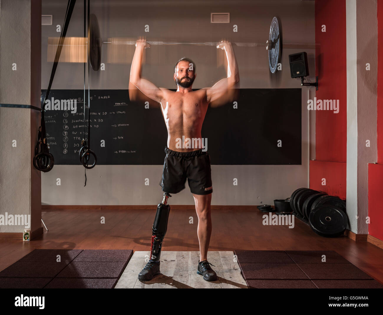 Man with a prosthesis training cross fit at the gym. - Stock Image