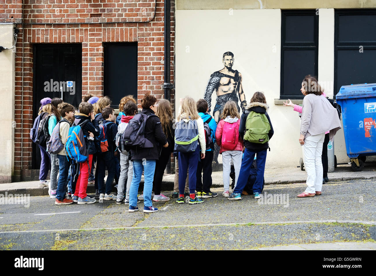A group of school children being shown graffiti in a city street - Stock Image