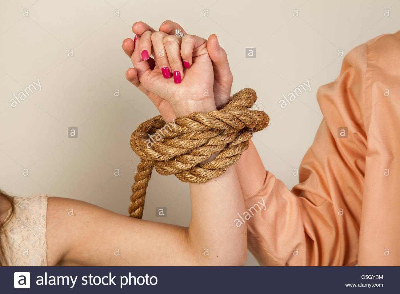 Close-up of a young couple's tied arms. - Stock Image