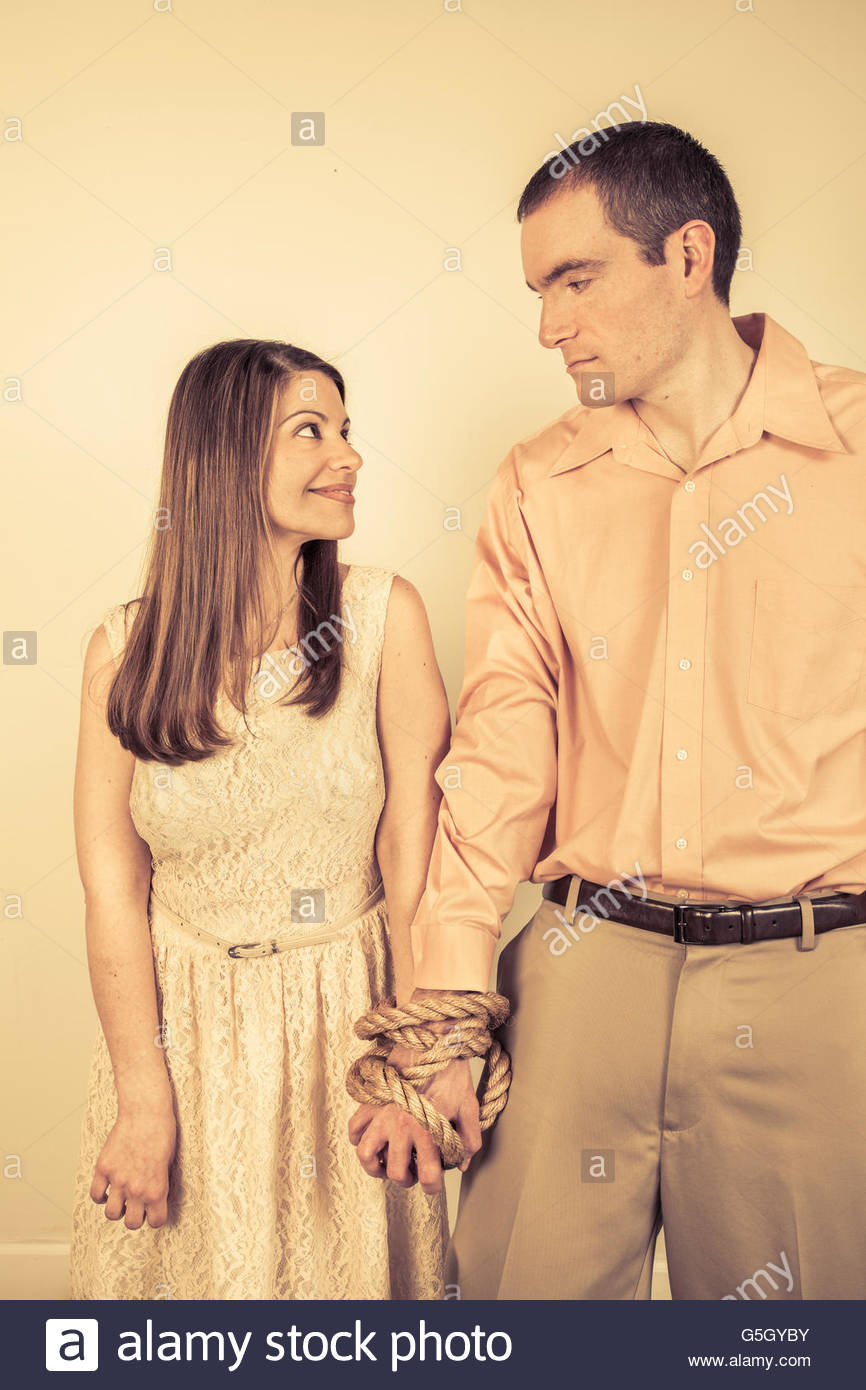 Young couple with their arms tied together. - Stock Image
