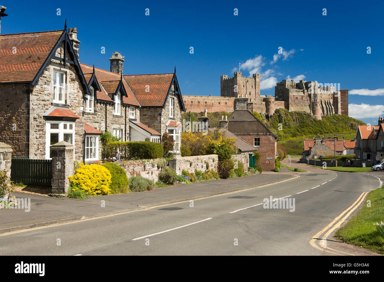 UK, England Northumberland, Bamburgh village, estate houses in Church Street with castle beyond - Stock Image