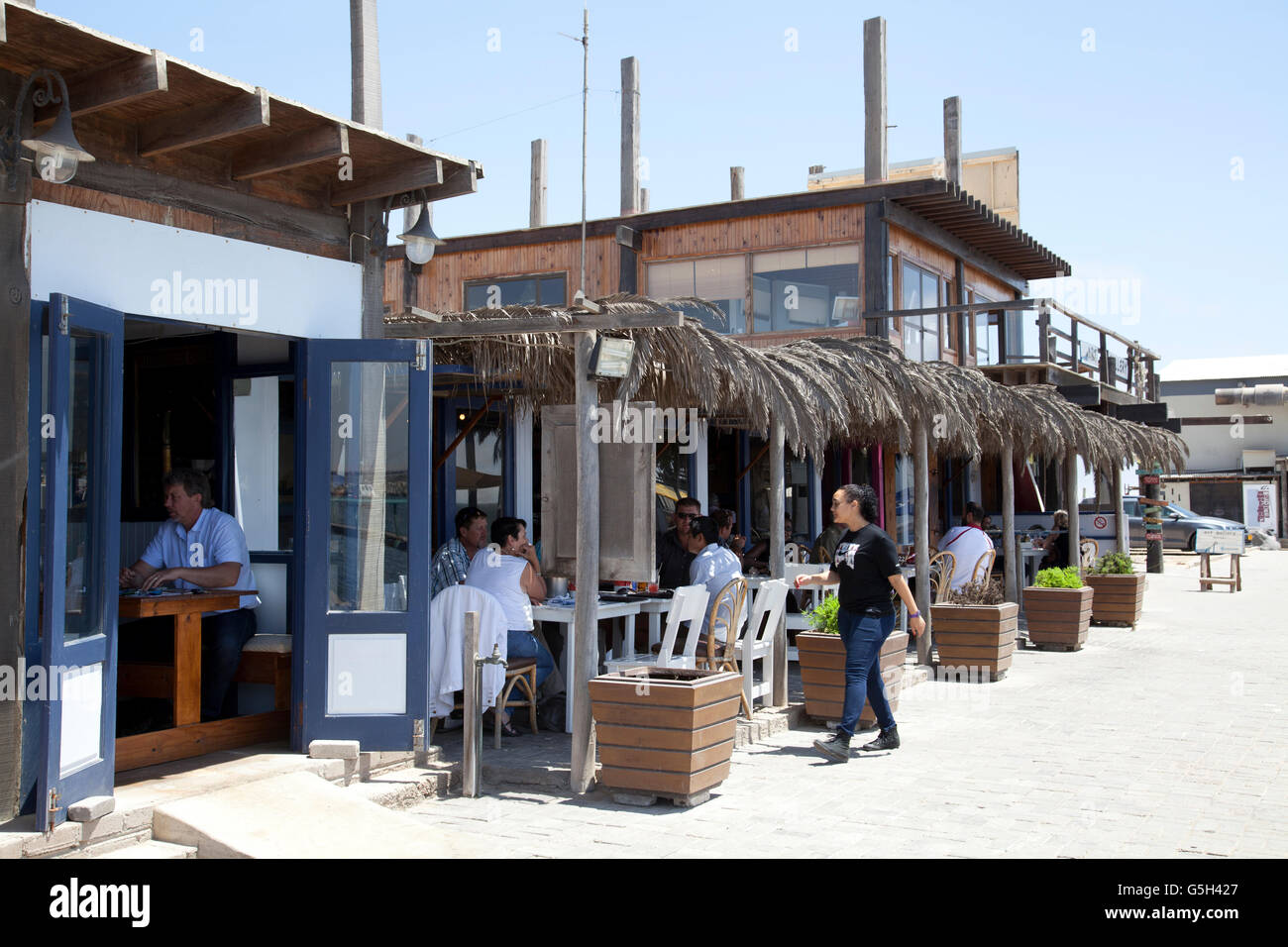 Anchors Restaurant with Diners on Walvis Bay waterfront in Namibia - Stock Image
