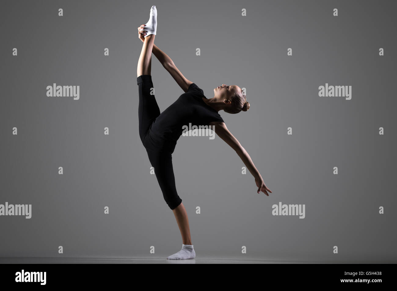 Beautiful cool young fit gymnast athlete woman in sportswear working out, dancing, doing balance rhythmic gymnastics - Stock Image