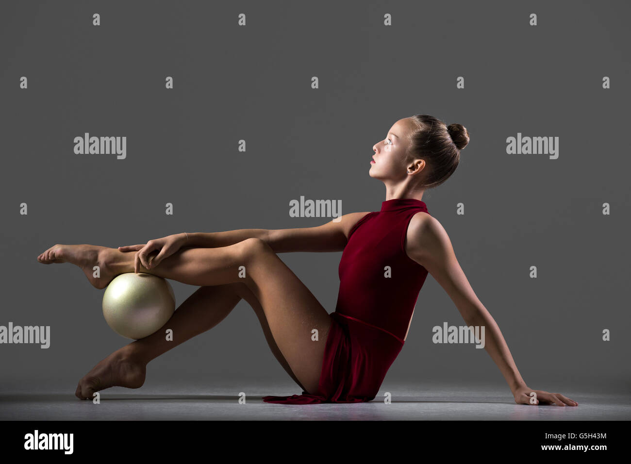 Beautiful cool young fit gymnast athlete woman in sportswear red dress working out, doing art gymnastics exercise - Stock Image