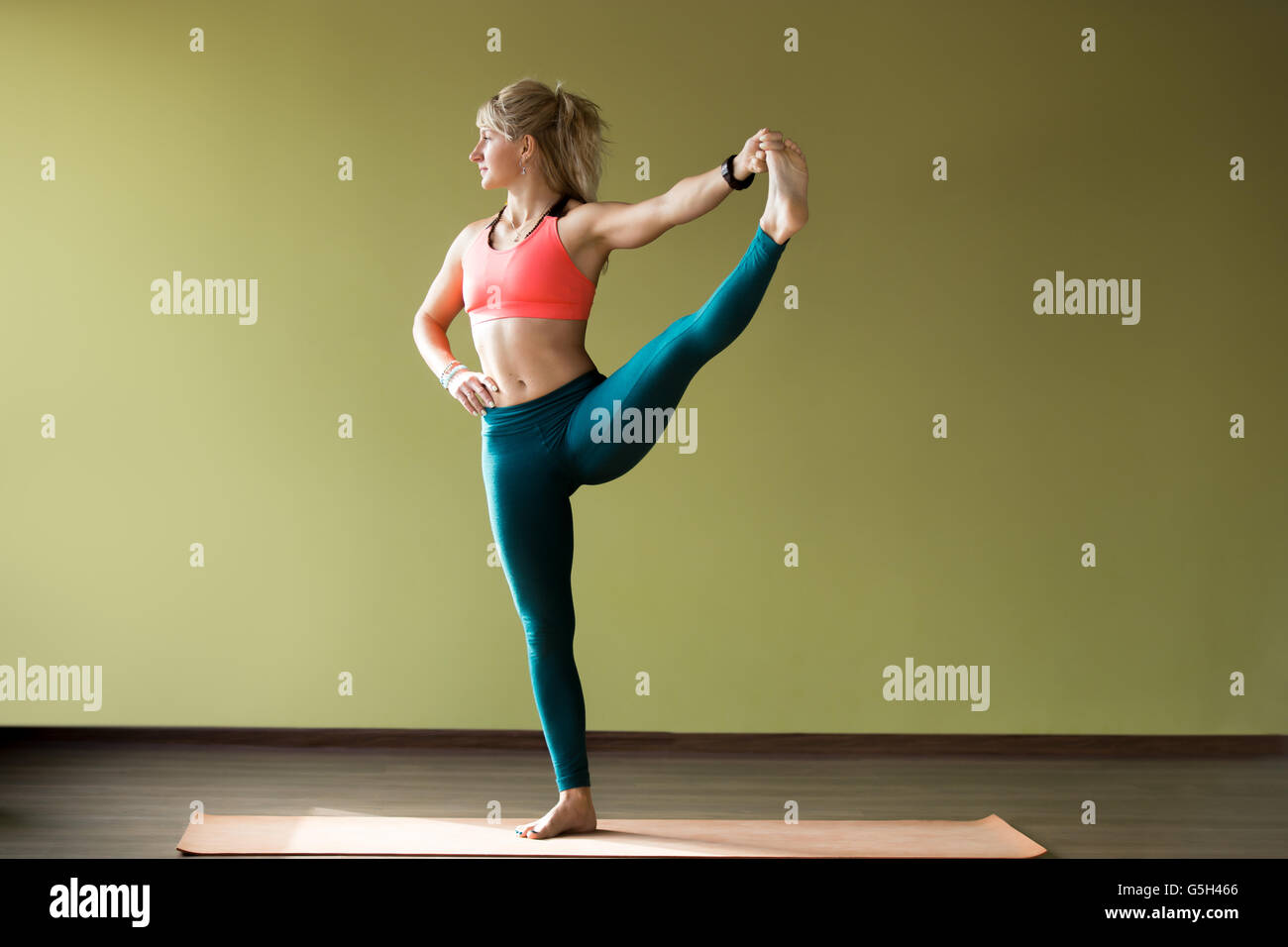 Sporty beautiful blond young woman in sportswear working out indoors, doing Utthita Hasta Padangustasana, Extended - Stock Image