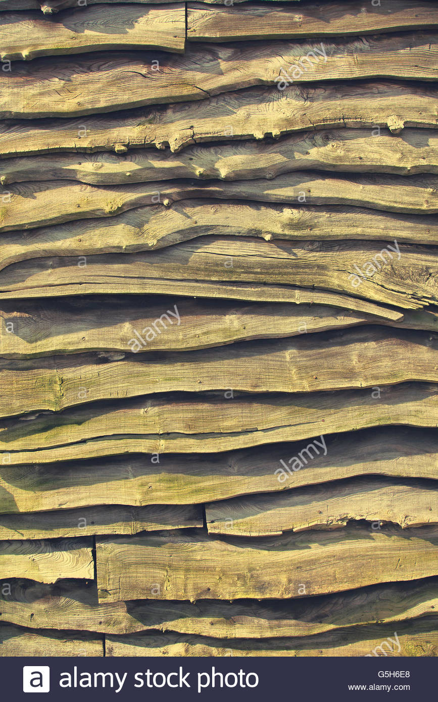 Natural Edged Planks of Wood Line Shed Exterior - Stock Image